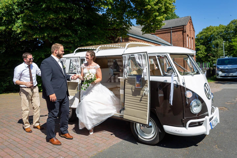 Hochzeitspaar steigt aus VW-Bulli aus