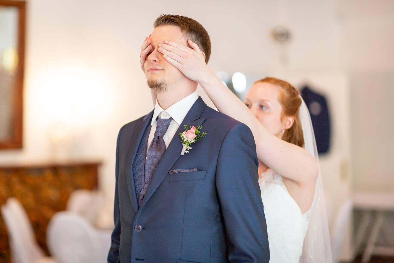First View - Braut hält Bräutigam die Augen zu.