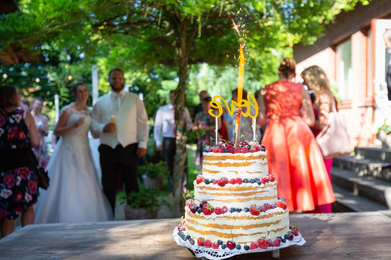 Hochzeitstorte mit Feuerwerk bei einer Sommerhochzeit im Landhaus-Stil