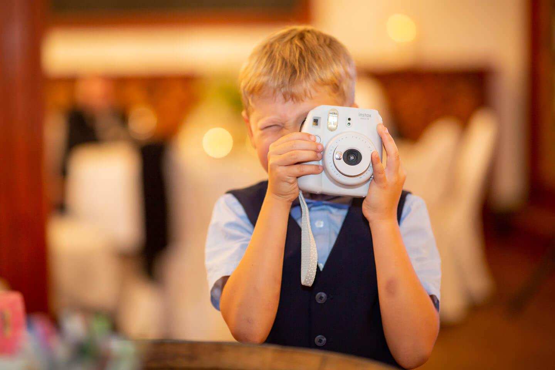 Junge fotografiert mit Polaroid-Kamera