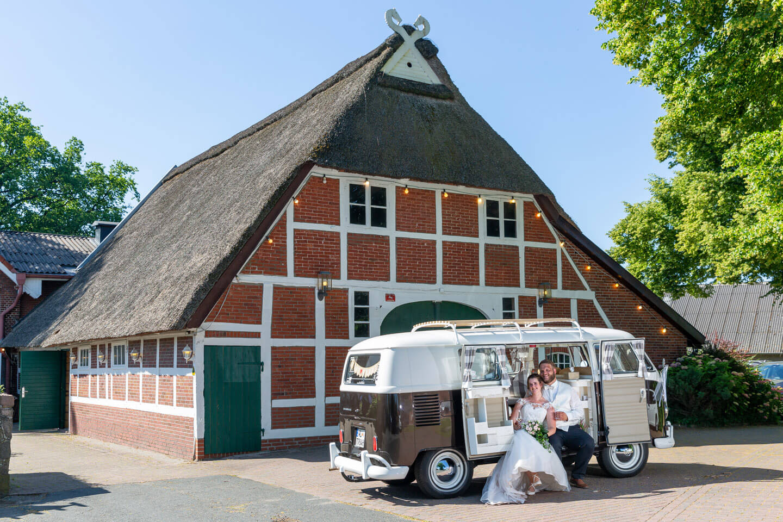 Sommerhochzeit im Landhaus-Stil. Brautpaar sitzt im VW-Bulli vor der Scheune
