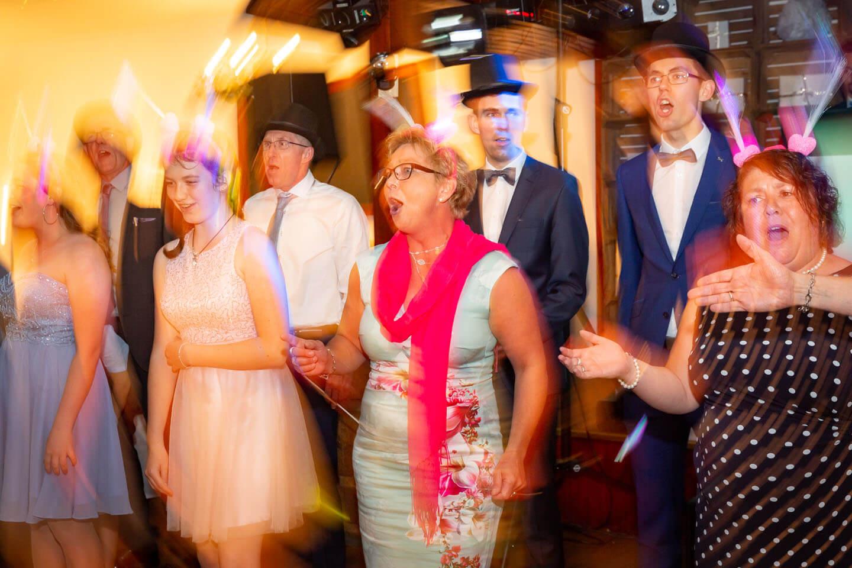 Hochzeitsgäste tragen ein Lied vor.