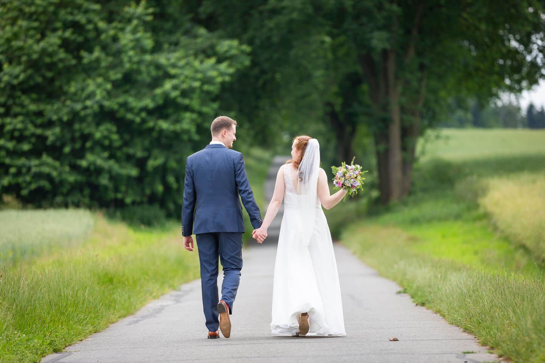 Natürliche Hochzeitsfotos - Paar geht Hand in Hand.