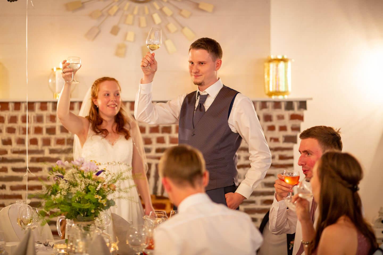 Cheers! Hochzeitspaar hebt das Glas.