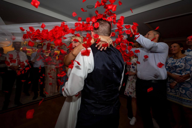 Rosenblätter fallen beim Schleiertanz auf das Hochzeitspaar
