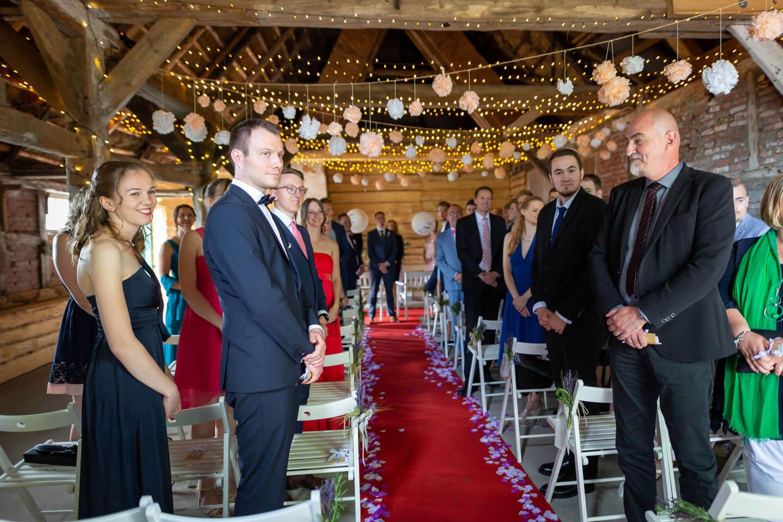 Hochzeitsgäste warten bei einer Scheunenhochzeit auf die Braut.