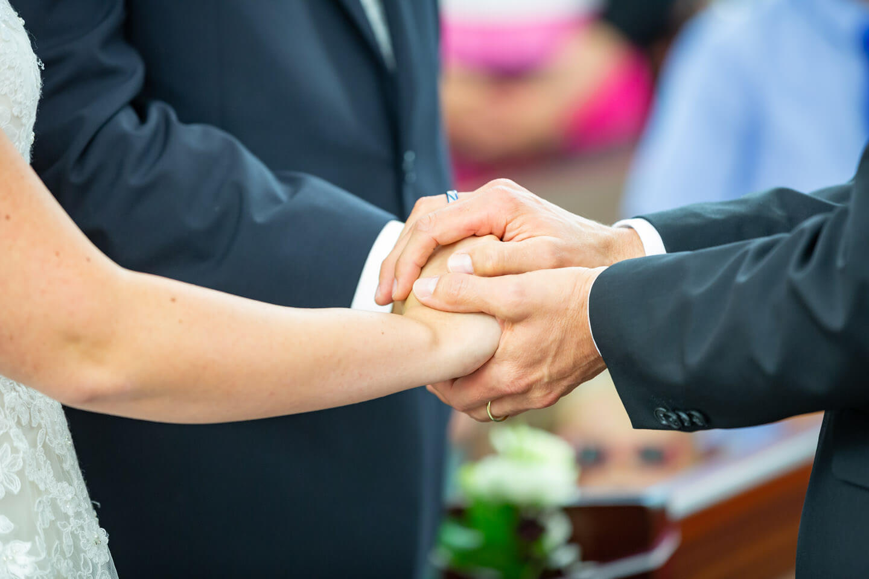 Die Hände von Pastor und Brautpaar während der Trauung