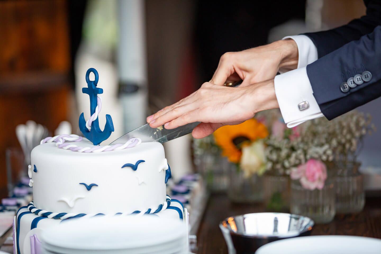 Anschnitt der Hochzeitstorte durch den Bräutigam