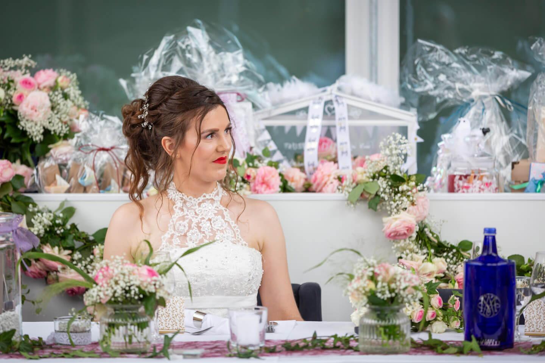 Braut sitzt inmitten einer liebevoll geschmückten Location