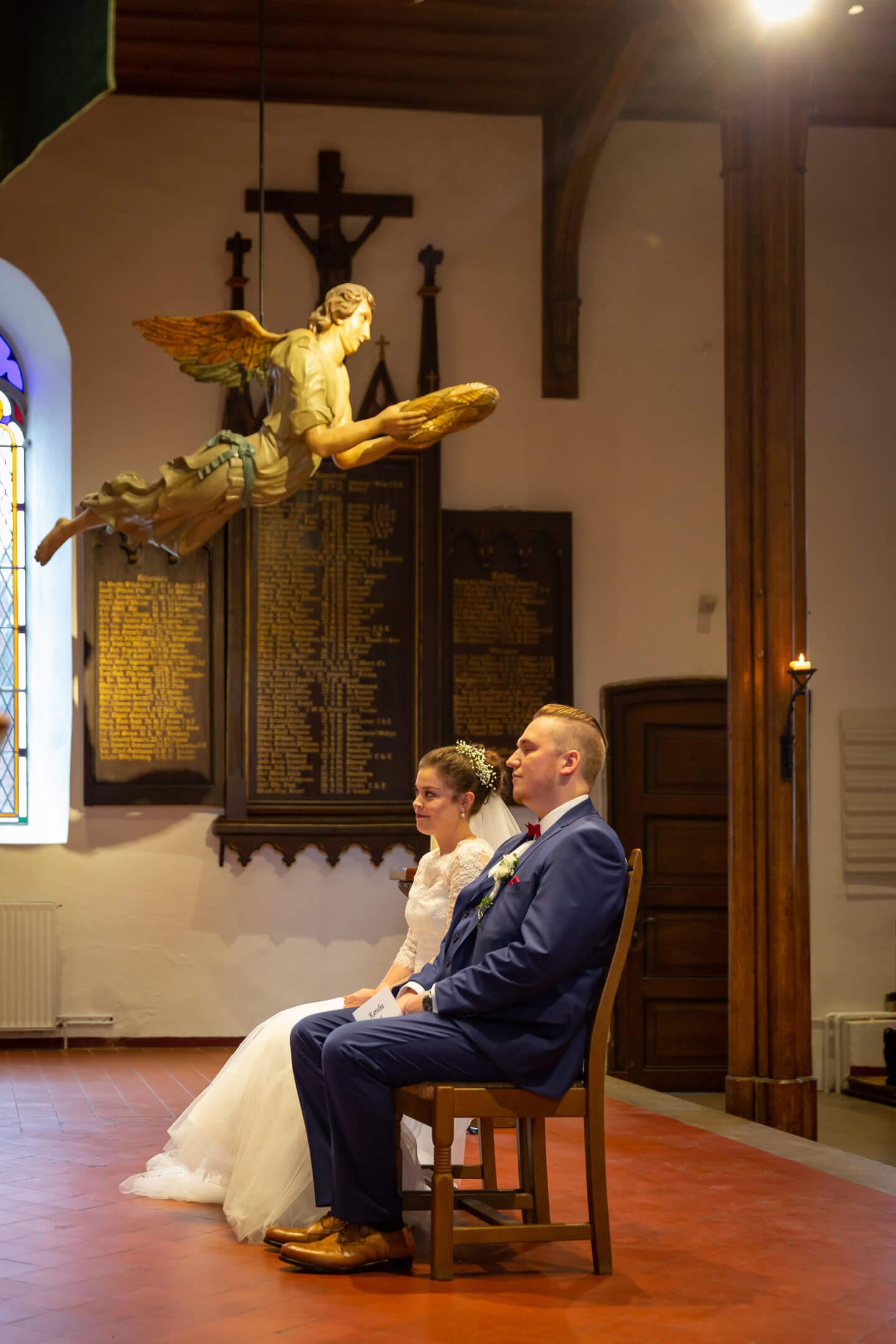 Brautpaar sitzt unter einem schwebenden Engel vor dem Altar in der Martin Luther Kirche in Trittau