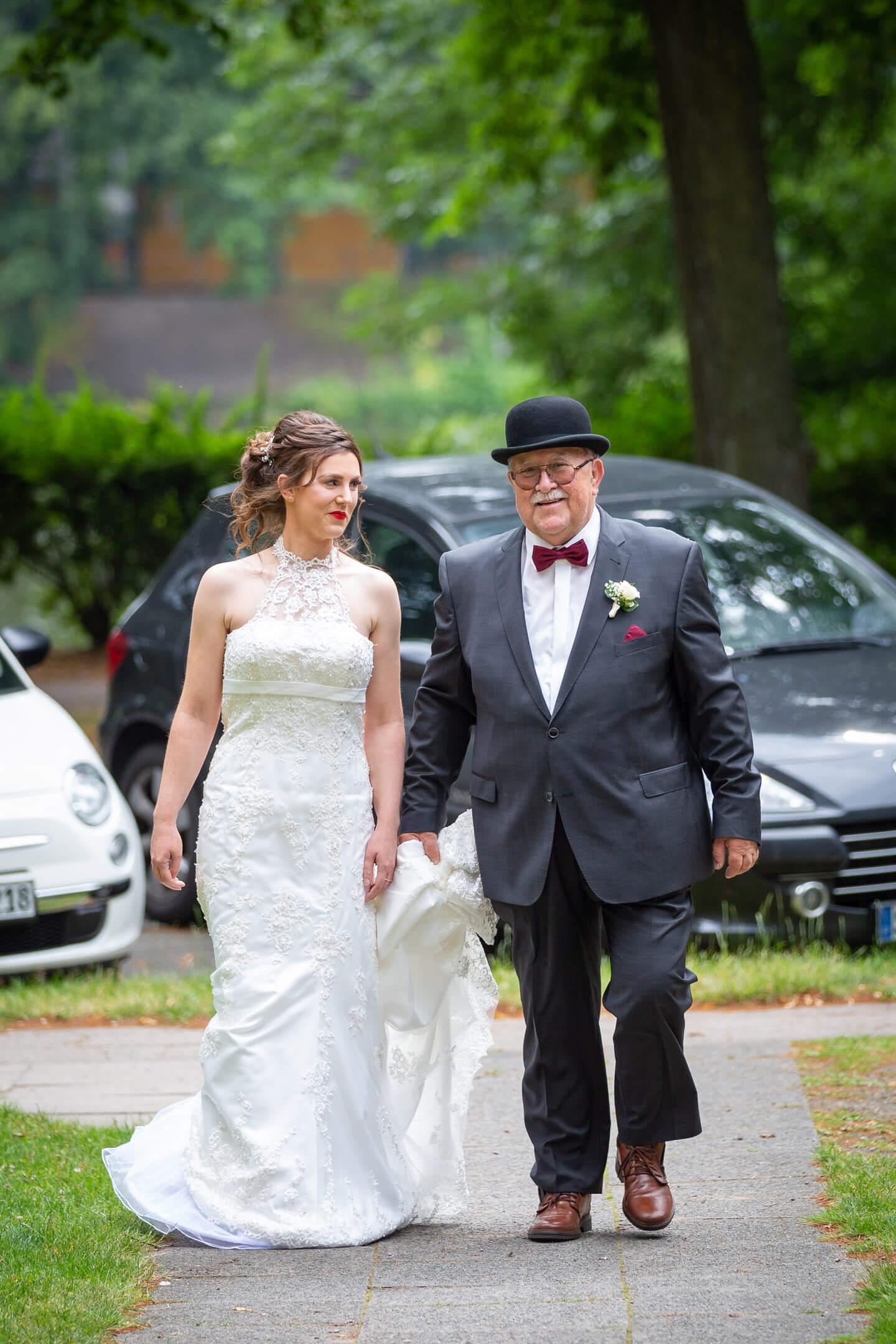 Brautvater führt seine Tochter zur Kirche