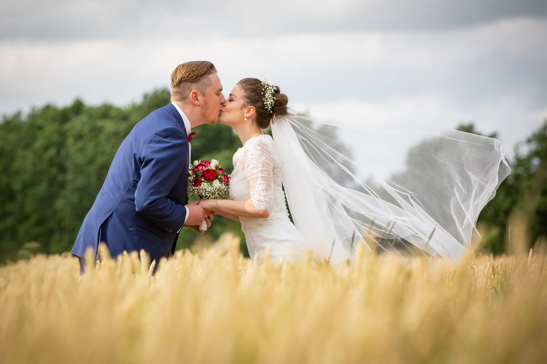 Brautpaar küsst sich im Kornfeld