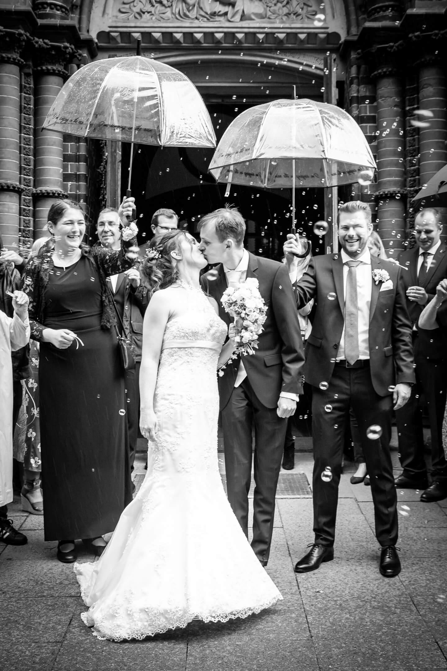 Just married - Hochzeitspaar küsst sich vor der Kirchentür (Fotograf: Florian Läufer)