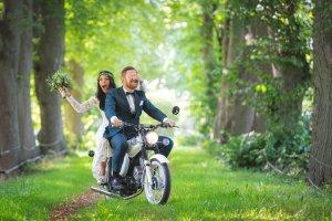 Natürliche Hochzeitsfotos - Brautpaar fährt auf einer Simsond durch eine Baumallee