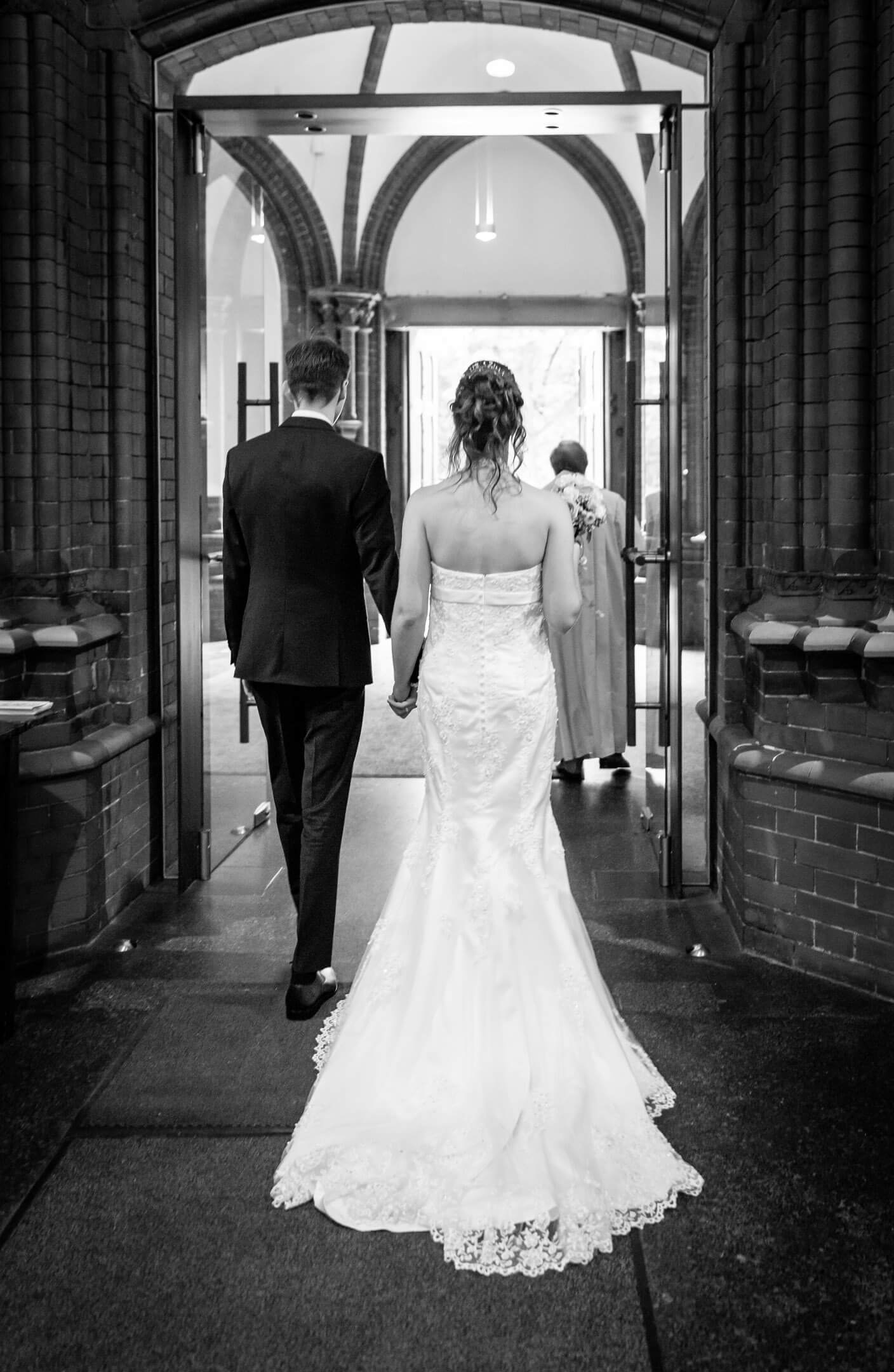 Brautpaar verlässt die Kirche. Das Brautkleid hat eine lange Schleppe.