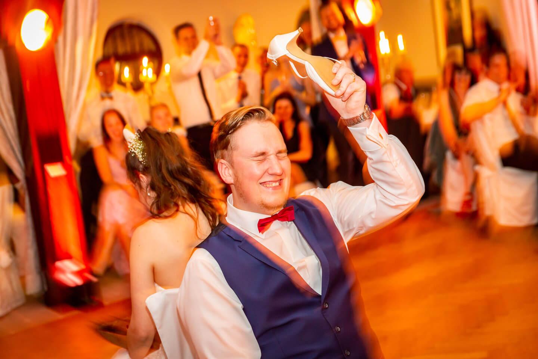 Das berühmte Schuhspiel auf einer Hochzeit. Bräutigam hält den Schuh der Braut hoch.