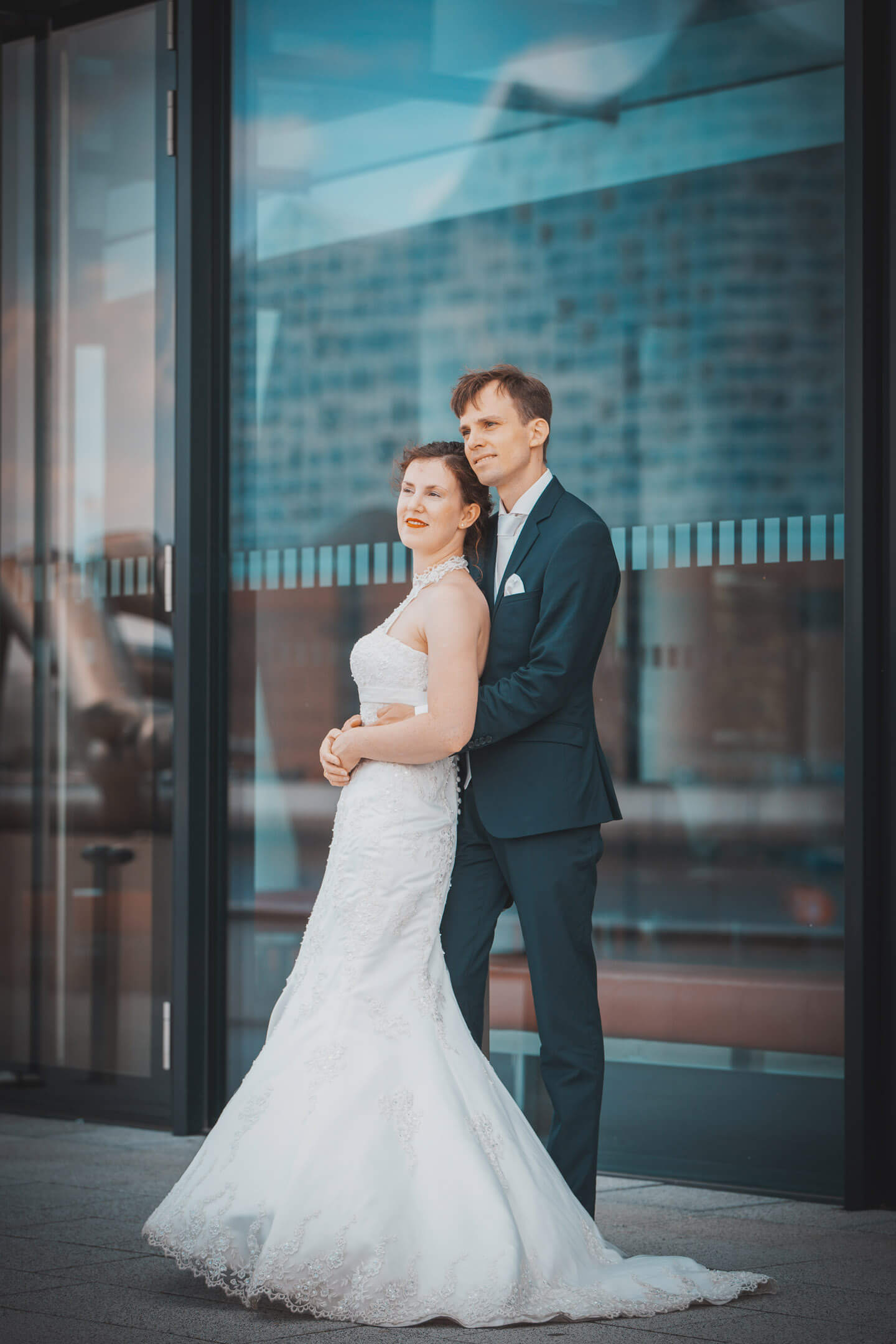 Brautpaar vor Glasfront in der sich die Elphi spiegelt
