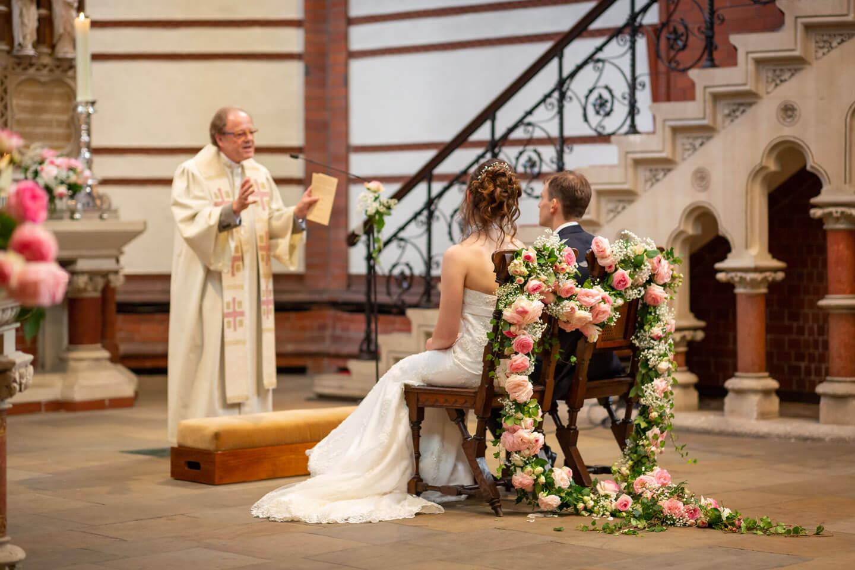 Brautpaar sitzt auf blumengeschmückten Stühlen