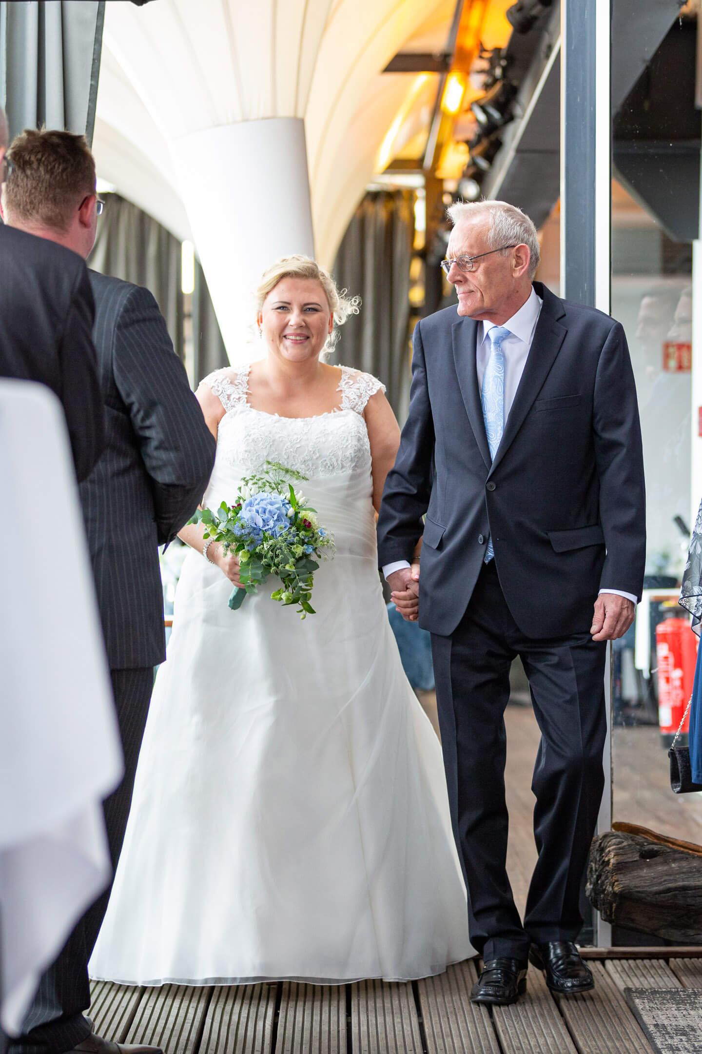 Braut wird von ihrem Vater zur Trauung begleitet