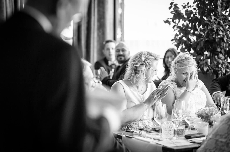 Braut wischt sich eine Träne aus dem Auge bei der Rede des Bräutigamvaters