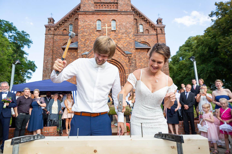 Brautpaar beim Hämmern vor der Kirche