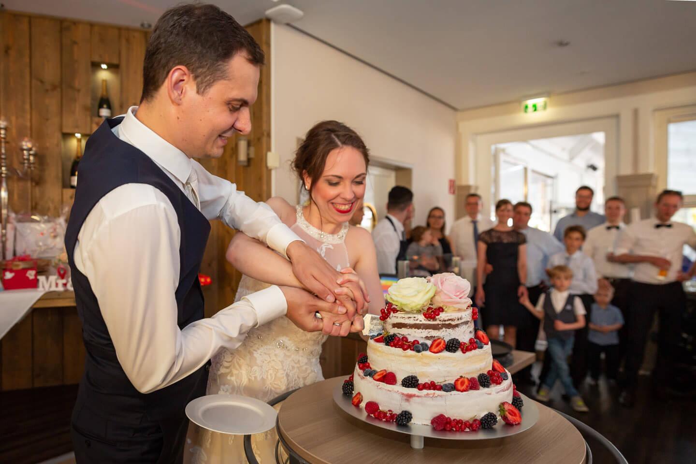 Die Hochzeitstorte wird angeschnitten.