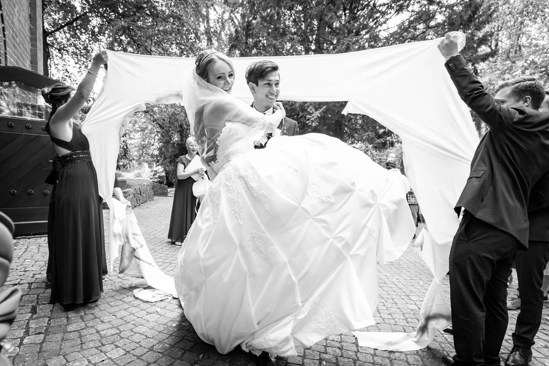 Bräutigam trägt seine Frau durchs ausgeschnittene Herz im Bettlaken