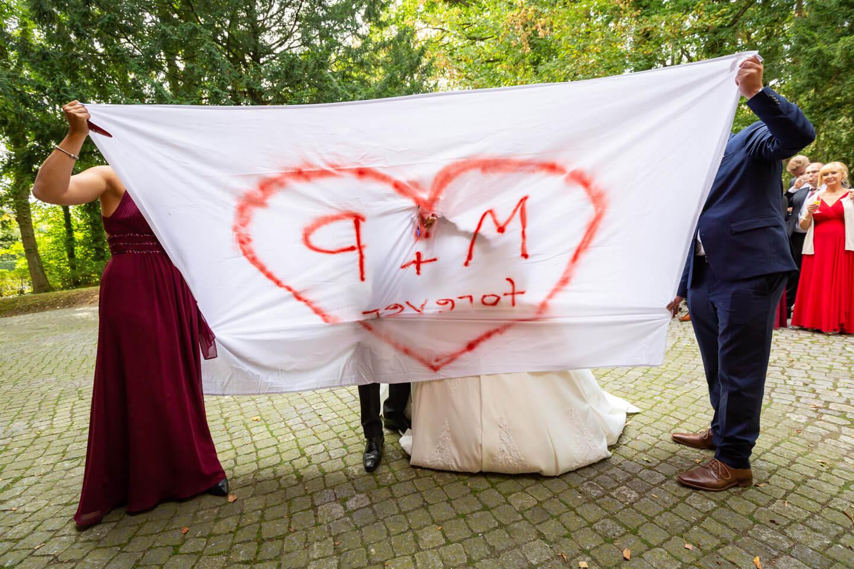 Hochzeitspaar schneidet aufgemaltes Herz aus dem Bettlaken aus