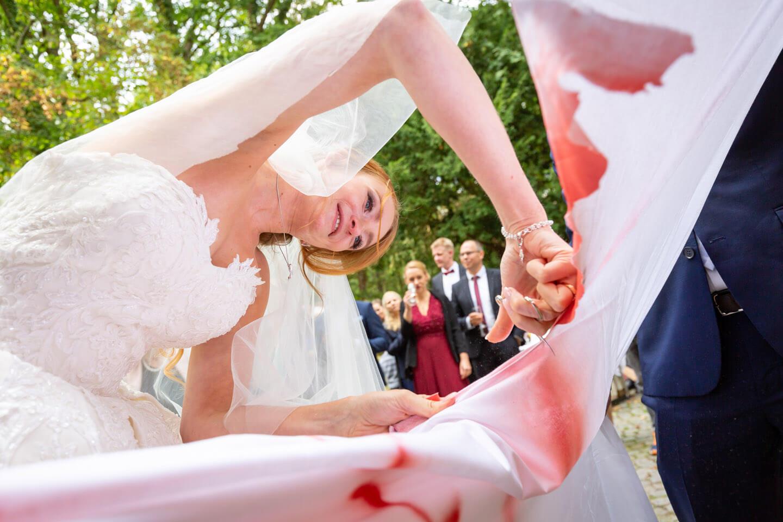 Braut schneidet mit Nagelschere Herz aus dem Bettlaken aus