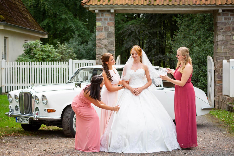 Brautjungfern mit Braut und Hochzeitsauto
