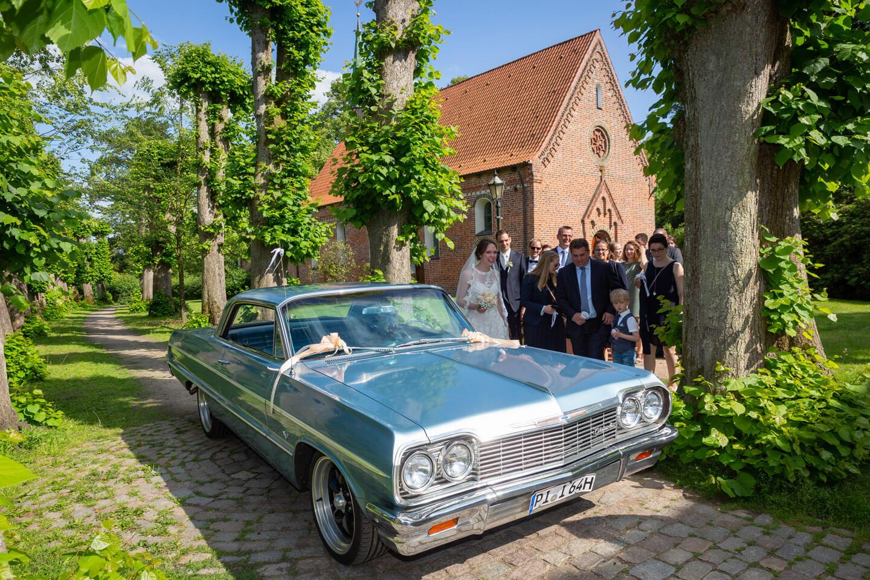 Hochzeitsauto steht vor der Kirche bereit.