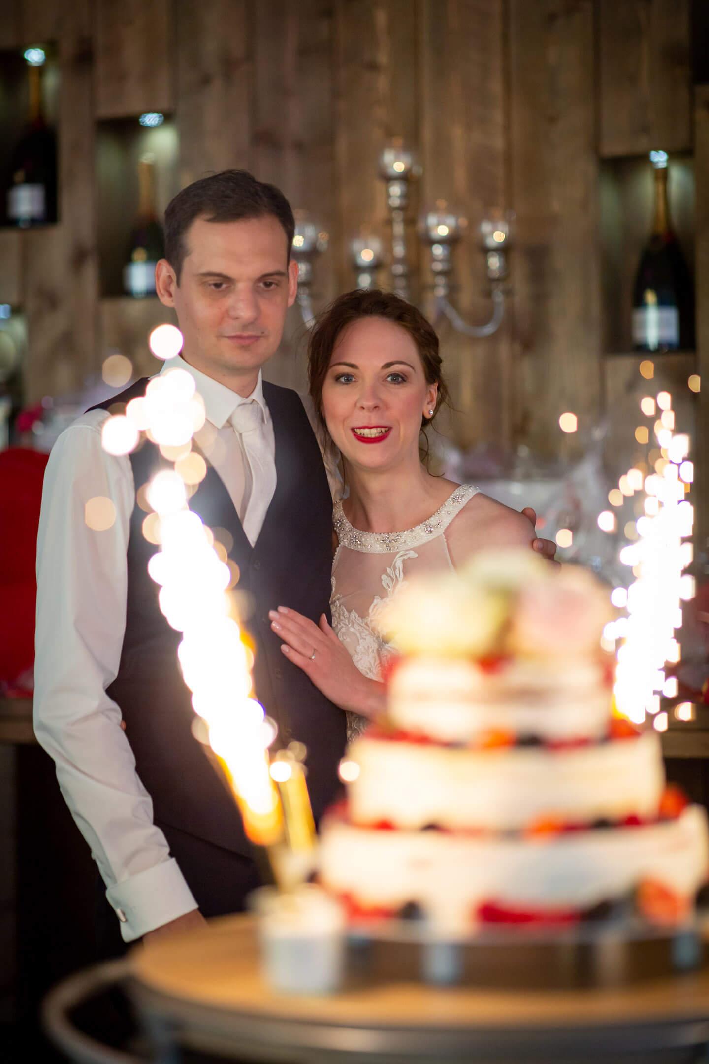 Brautpaar blickt auf die Hochzeitstorte mit Feuerwerk.