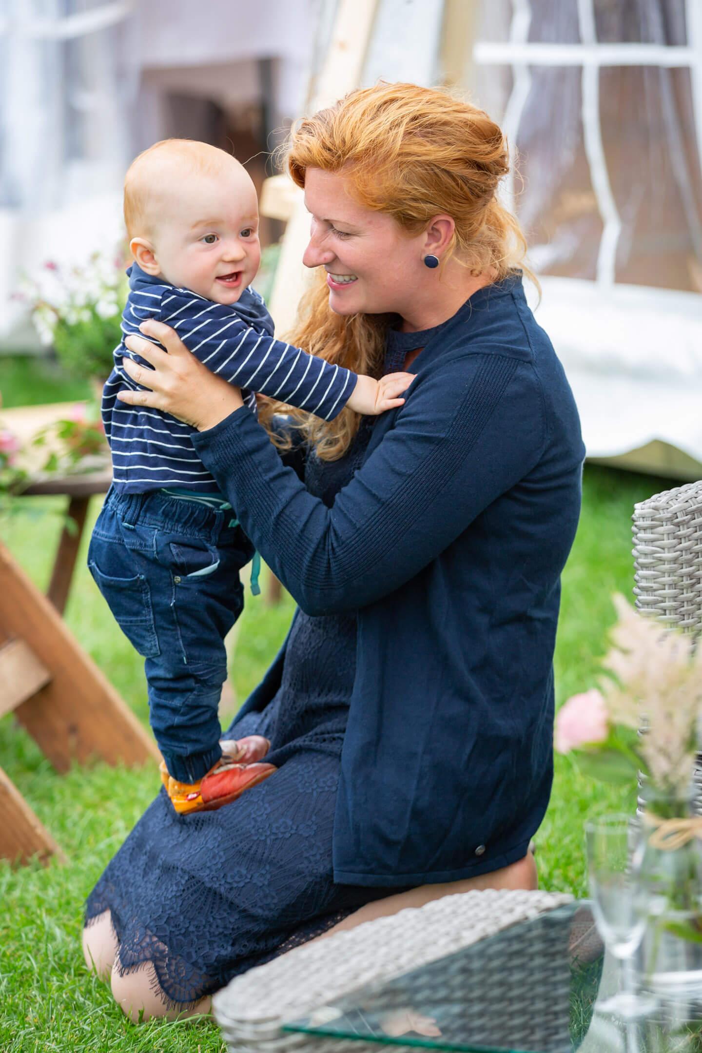 Mama mit ihrem Baby auf einer Gartenhochzeit