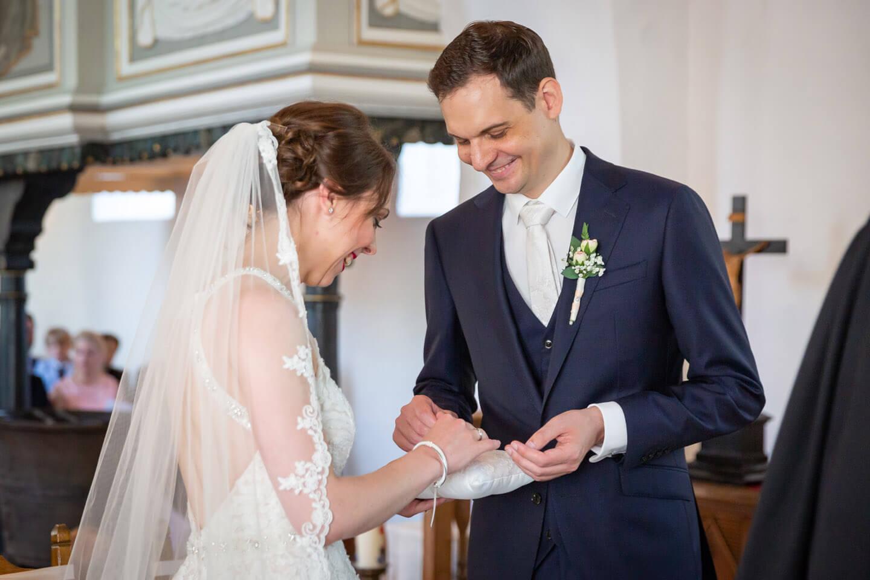 Brautpaar nimmt die Trauringe vom Ringkissen