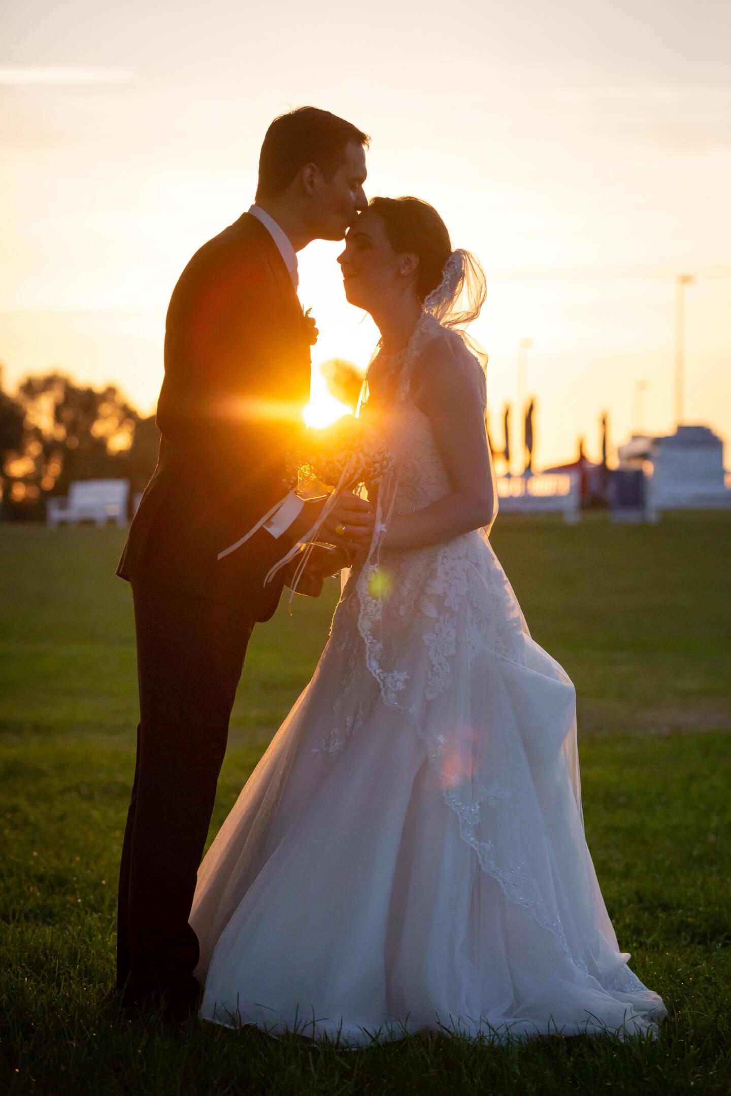 Bräutigam küsst seiner Braut im Sonnenuntergang auf die Stirn.