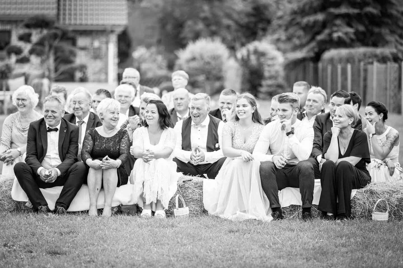 Gäste sitzen bei freier Trauung auf Heuballen