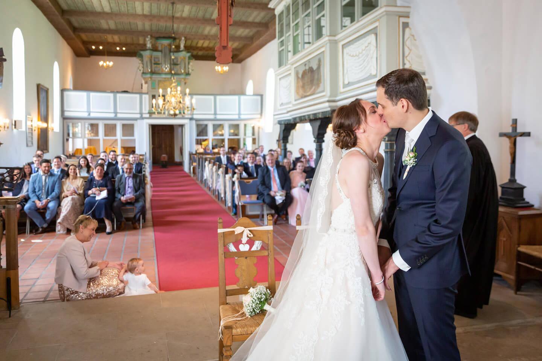 Brautpaar gibt sich den Vermählungskuss bei ihrer kirchlichen Trauung