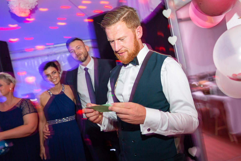 Bräutigam liest beim Hochzeitsspiel etwas vor