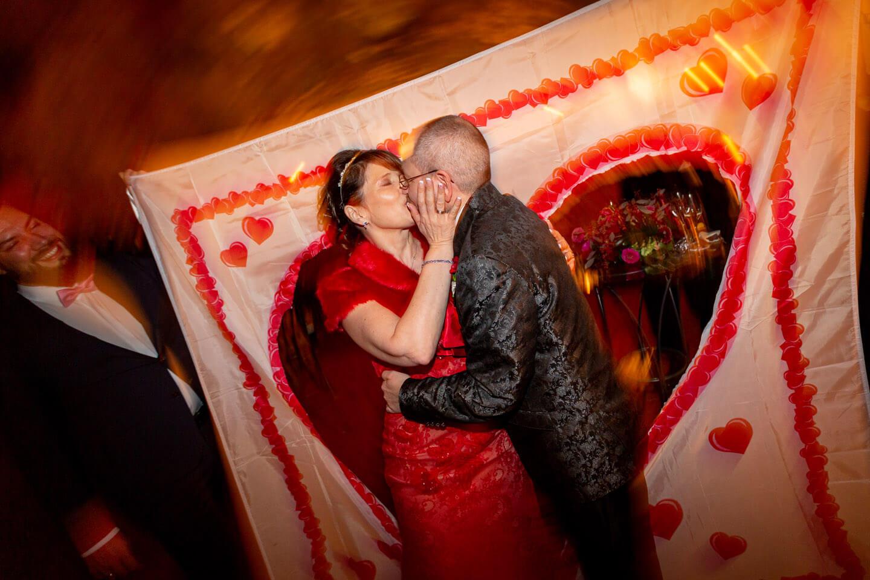 Brautpaar schreitet durch das ausgeschnittene Herz eines Bettlakens