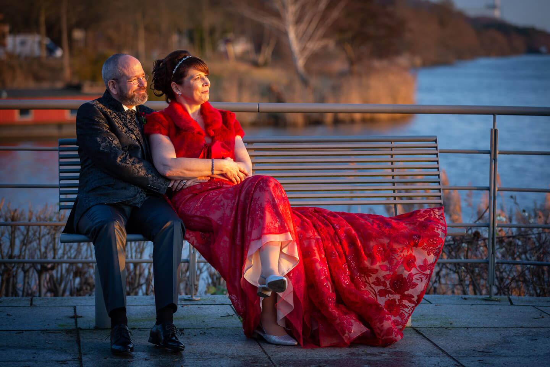 Hochzeitspaar auf einer Parkbank im Sonnenuntergang an der Elbe