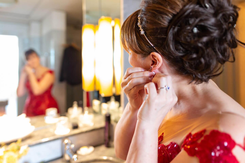 Braut legt Ohrringe vor dem Spiegel an.