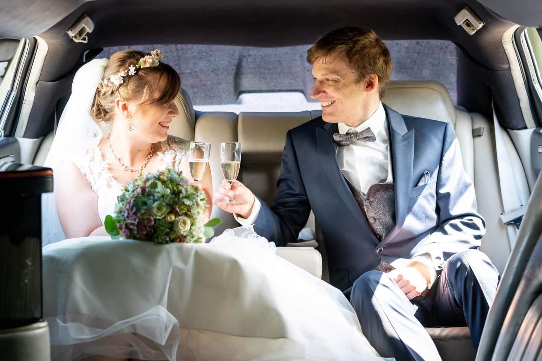 Brautpaar trinkt ein Glas Sekt im Hochzeitsauto