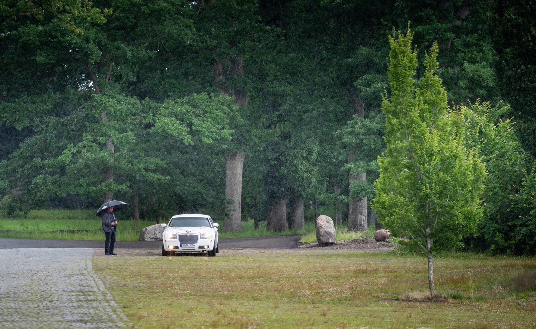 Limousine mit Hochzeitspaar steht im Regen
