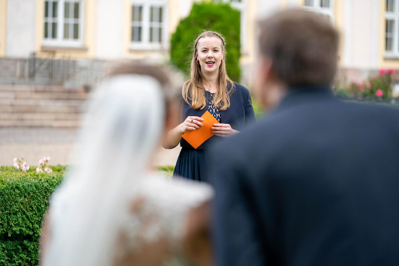 Trauzeugin erklärt dem Hochzeitspaar ein Spiel