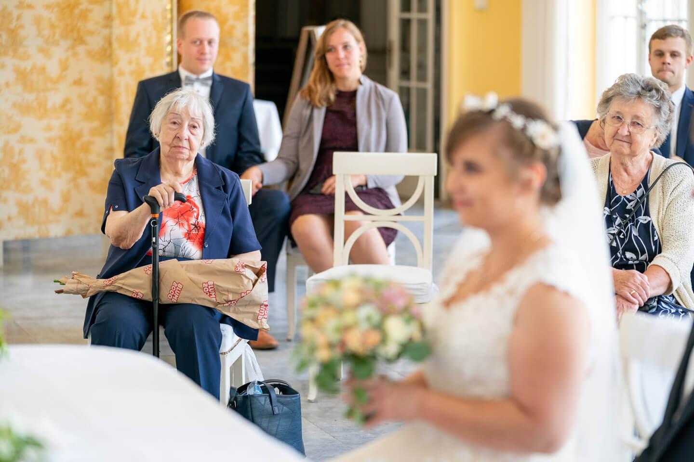 Großmutter blickt auf die Braut bei der standesamtlichen Trauung