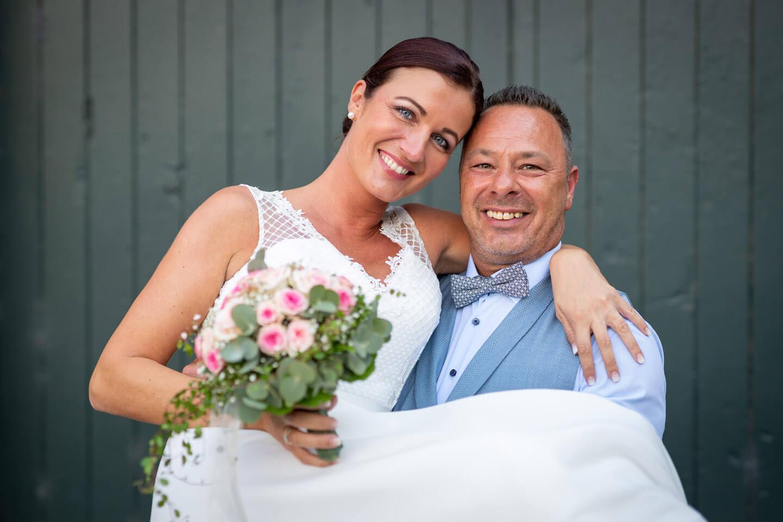Bräutigam trägt die Braut auf Händen.
