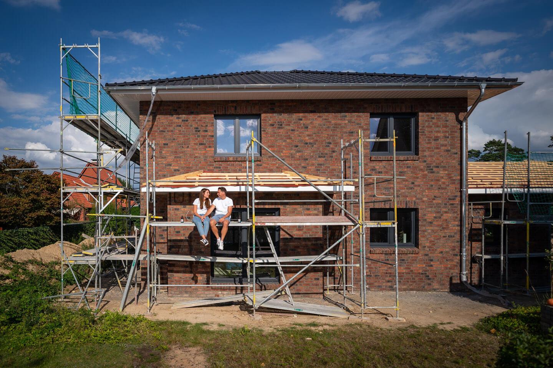 Verlobungspaar sitzt auf dem Baugerüst ihres Hauses
