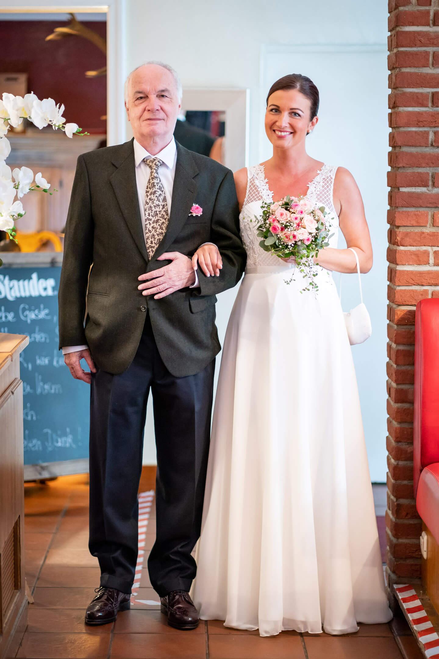 Braut mit Brautvater auf dem Weg zur Trauung