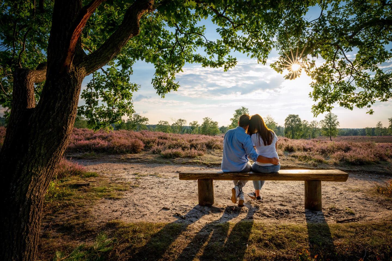 Paar sitzt auf einer einsamen Bank in der Heide und genießt die Abendsonne. Entstanden bei einem Engagement-Shooting