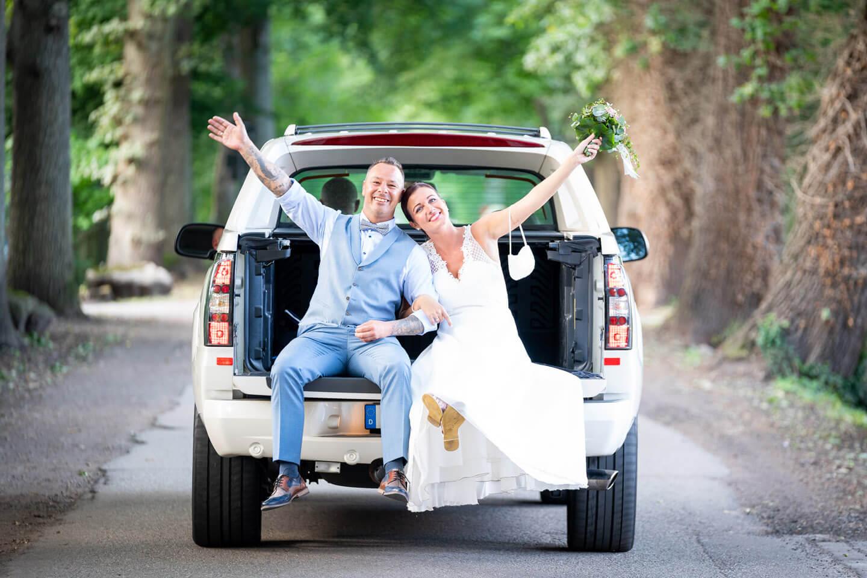 Hochzeitspaar auf der Ladefläche eines Cadillac Escalade